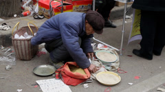 An old man sell some food in street market.china. - stock footage