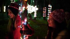 Teen Girls Frolic Single File In A Forest of Trees Lit For The Holidays Stock Footage