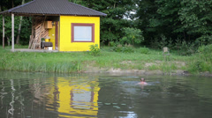 Yellow bathhouse to the village pond shore man climbs to shore Stock Footage