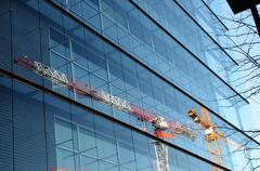 Two cranes are reflected in a glass wall of building Stock Photos