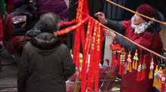 Joss sticks and articles for use to pray sold at a market - stock footage