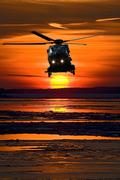 helicopter at sunset - stock photo