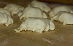 homemade dumplings lying on a plank prepared for cooking - stock photo