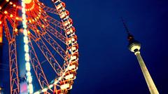 Illuminated ferris wheel near GDR tower in Berlin. Stock Footage