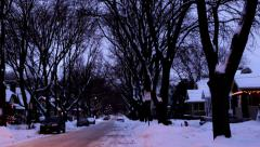 Time lapse: Dusk on a snowy residential street, holiday lights glow Stock Footage