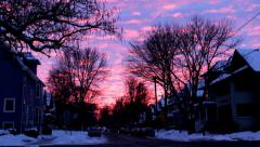 Time lapse: Sunset clouds over a snowy street with traffic and holiday lights Stock Footage