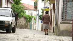 Woman carrying laundry on her head Stock Footage