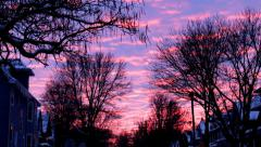 Time lapse: Bright sunset over a snowy residential street framed by trees Stock Footage