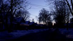 Time lapse: Dusk on a snowy residential street, holiday lights and sunset - stock footage
