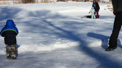 Family trying to shovel snoww of the lake for iceskating. Stock Footage