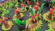 Stock Video Footage of waving of leaves props of Fish, flower and fruits costumed street dancers
