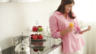 Stock Video Footage of Cute young woman standing in kitchen using touchpad drinking juice