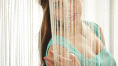 Charming lady standing behind beaded curtains looking at camera and smiling.  - stock footage