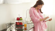 Stock Video Footage of Charming girl standing in kitchen using touchpad looking at camera and smiling