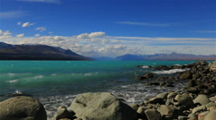 Slow motion waves crashing on the shore of blue lake in New Zealand Stock Footage