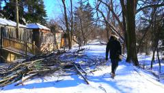 Man walks past fallen tree damage from winter ice storm Stock Footage