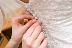 hands of a person help to a bride to clasp buttones of the dress - stock photo
