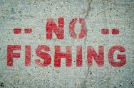 Stock Photo of no fishing sign on cement