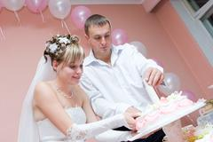 Newly married couple with knife cut wedding cake Stock Photos