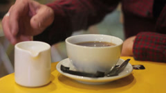 Milk is poured into tea in a cafe Stock Footage