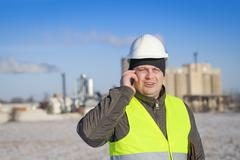 Engineer with cell phone near the factory in winter Stock Photos