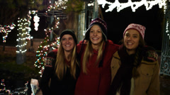 Three Teens Walking In A Winter Wonderland Of Holiday Lights – Slow Mo - stock footage