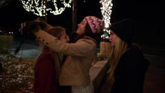 Teen Girl Humorously Helps Her Friend With Her Hat In A Holiday Setting Stock Footage