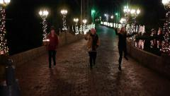 Winter Holidays: Teen Girls Run, Jump, Twirl w/Sparklers on Lit Cobblestone St. Stock Footage