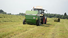 Cut grass compress equipment rides through the field work Stock Footage