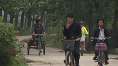 Chinese people cycling in rural China Stock Footage