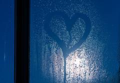 moonlight through the window. sweaty glass and heart - stock photo