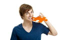 young man holding and biting a puzzle piece, isolated on white background - stock photo