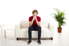 young man sitting on the couch - stock photo