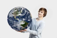 Handsome young man holding the planet earth on its hands, isolated on white Stock Photos