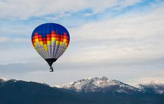 multicolored balloon in the blue sky - stock photo