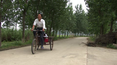 A local villager riding by on his bike in rural China Stock Footage