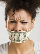 covering mouth with a dollar banknote - stock photo
