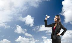business woman throwing a paper plane - stock photo