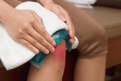 a woman applying cold pack on  swollen hurting knee after accident - stock photo