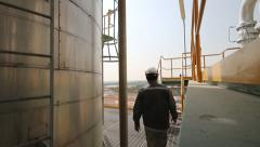 Engineer walking in refinery plant - stock footage