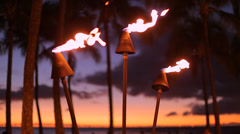 Tropical Hawaii fire torch tiki evening sunset palm trees sky Stock Footage