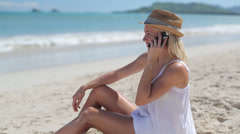 Caucasian woman on beach vacation talking on cellphone - stock footage