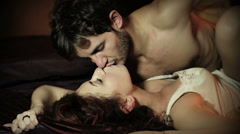 Sexy young couple kissing and playing in bed Stock Footage