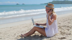 Caucasian woman on beach vacation using laptop and cellphone Stock Footage