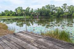 old wooden platform facing to lake - stock photo