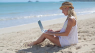 Stock Video Footage of Caucasian woman on beach vacation using laptop pc
