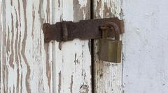 Peeling wooden door secured by padlock hasp and staple Stock Photos