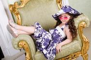 Stock Photo of small beauty in sunglasses on the armchair