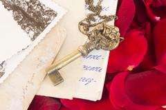 key with old papers and  rose petals - stock photo