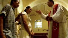 Priest administers Sacrament of Confirmation low angle Stock Footage